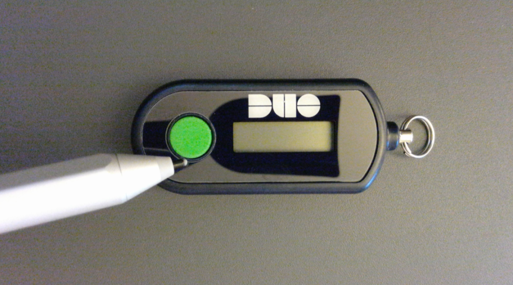 Pointer indicating the location of the green button on the bottom (or left) side of the device.